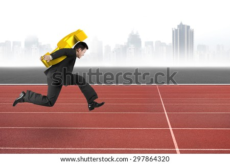 Businessman carrying 3D golden dollar sign running on red track, with gray city skyline background.