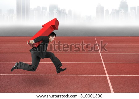 Businessman carrying 3D red arrow up running on track, with gray city skyline background.