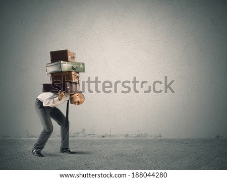 Businessman carrying heavy suitcases. concept of difficulty - stock photo