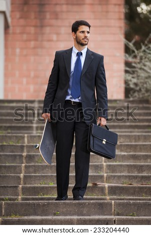 Businessman carrying his skateboard - stock photo