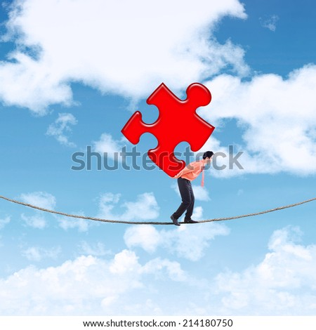 Businessman carrying puzzle while walking on the rope over a mountain