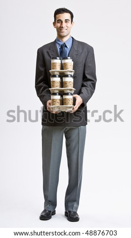Businessman carrying stack of coffee cups - stock photo