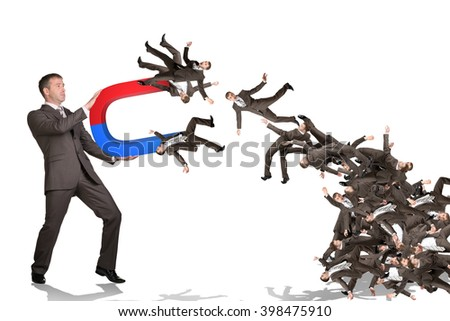 Businessman catching people on magnet - stock photo