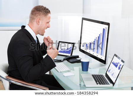 Businessman celebrating a performance graph sitting at his desk with statistical reports spread over three monitors cheering and clasping his fists - stock photo