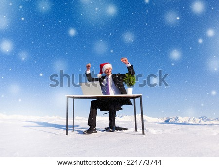 Businessman celebrating christmas on snow covered mountain.
