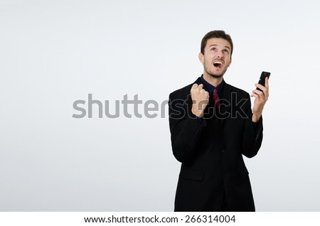 Businessman celebrating with cell phone in hand - stock photo