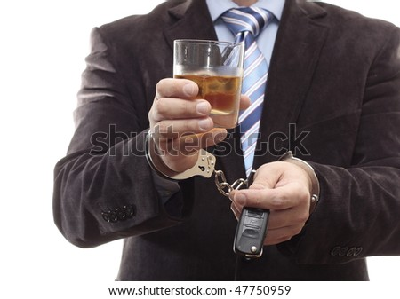 Businessman chained in handcuffs with car keys and a drink in hand