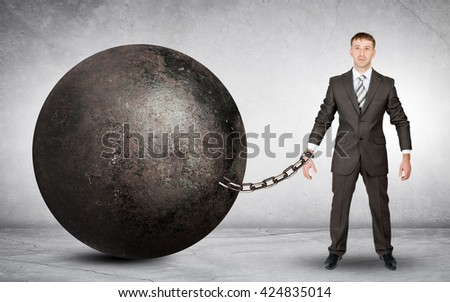 Businessman chained to large ball on grey background - stock photo