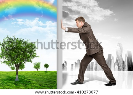 Businessman changing nature landscape on grey city