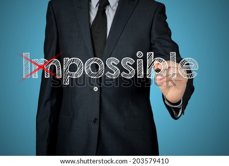 Businessman changing word impossible into possible on virtual background  - stock photo