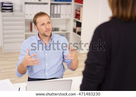 Businessman chatting to a female colleague or supervisor standing over his desk gesturing with his hands as he looks up with a serious expression