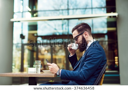Businessman checking email and drinking coffee. - stock photo