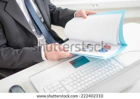 Businessman checking financial graphs at the office
