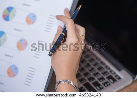 Businessman checking graph with a laptop, phone and alarm clock on the table when the morning light.