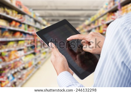 Businessman checking inventory in minimart on touchscreen tablet - stock photo