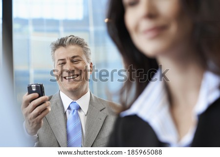 Businessman checking mobile phone near colleague - stock photo