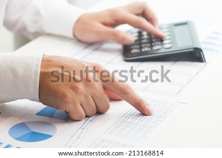 Businessman checking numbers on a document - stock photo
