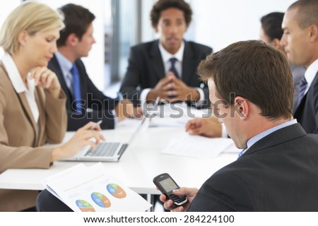 Businessman Checking Phone During Meeting In Office - stock photo