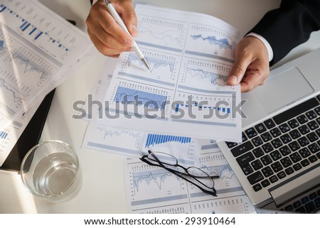 Businessman checking reported profits on the paper. - stock photo