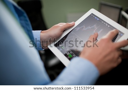Businessman checking stock market on tablet - stock photo