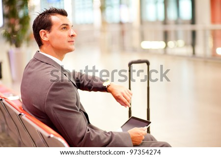 businessman checking time and using tablet at airport - stock photo