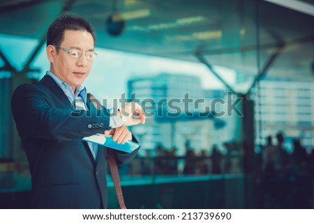 Businessman checking time on his watch while standing at the airport - stock photo