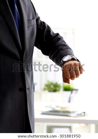 Businessman checking time on his wristwatch. men's hand with a watch - stock photo