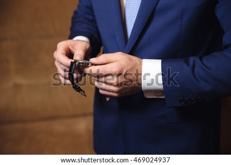 Businessman checking time on his wristwatch. men's hand with a watch.