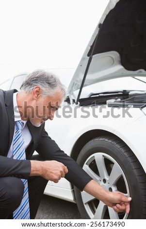 Businessman checking tire of his car - stock photo