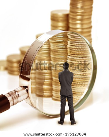 Businessman checks the money with magnifying glass - stock photo