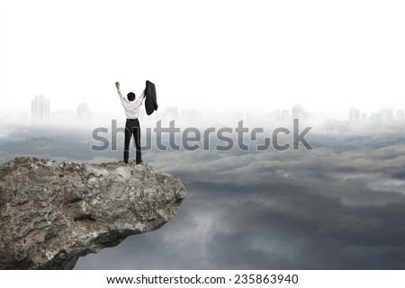 businessman cheering on cliff with gray cloudy sky cityscape background - stock photo
