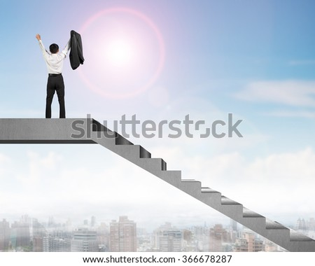 Businessman cheering on top of concrete stairs with city view in sunny day