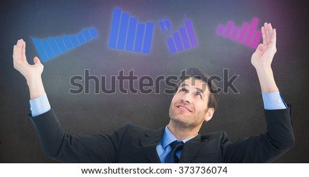 Businessman cheering with hands raised against grey room - stock photo