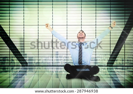 Businessman cheering with tablet sitting on floor against window overlooking city - stock photo