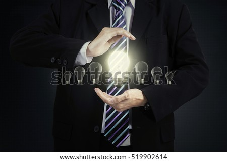 Businessman chooses one bright lamp on his hands, concept of new innovation