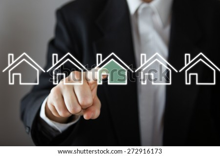 Businessman choosing house, real estate concept. Hand pressing the house icon. Copy space