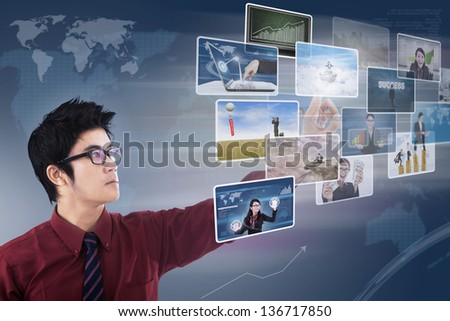 Businessman choosing photos on touchscreen with world map background - stock photo
