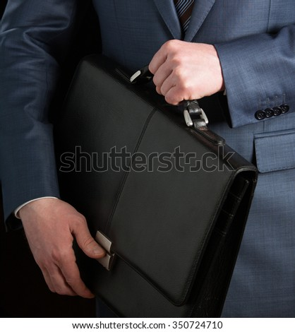 Businessman clasping briefcase to his breast on black background