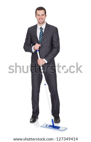 Businessman cleaning floor. Isolated on white background - stock photo