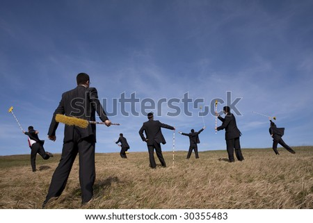businessman cleaning the field with a broom (some sharp, some with motion blur) - stock photo