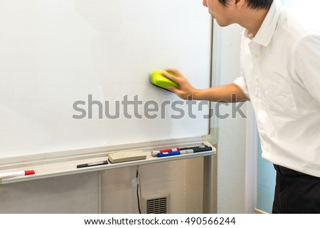 Businessman cleaning whiteboard