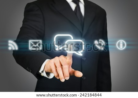 Businessman clicking on live chat icon - stock photo