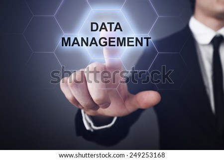 businessman clicks on virtual touchscreen display and select data management - stock photo