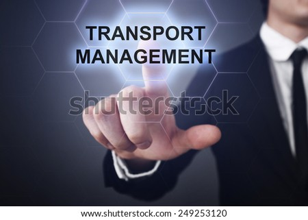 businessman clicks on virtual touchscreen display and select transport management - stock photo