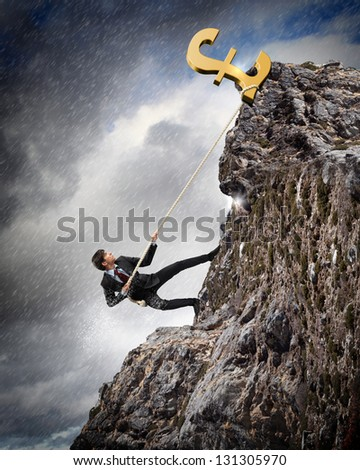 businessman climbing hill with pound on top