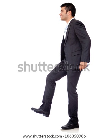 Businessman climbing imaginary stairs - isolated over a white background