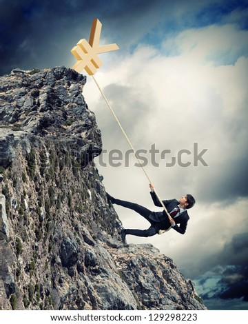 businessman climbing mountain with yen on top