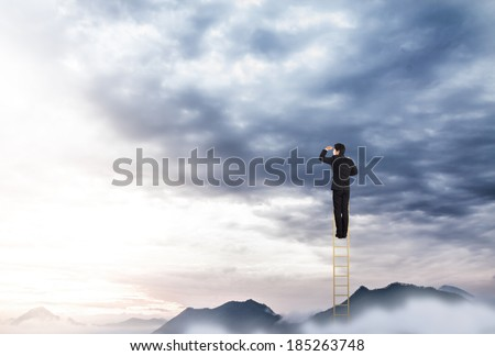 Businessman climbing on a ladder over mountain looking ahead - stock photo