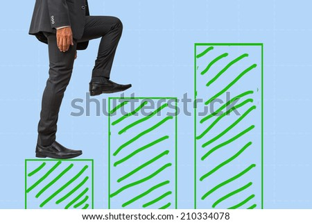 businessman climbing on bar graph to success    - stock photo