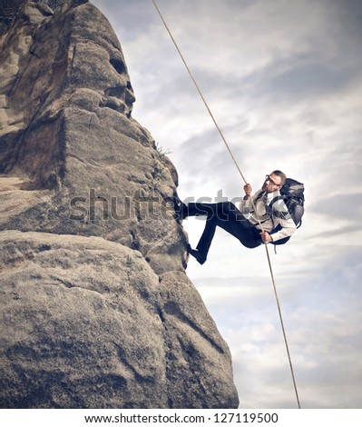 businessman climbing on mountain with rope and backpack - stock photo